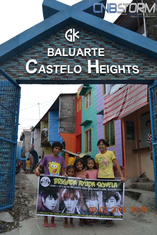 Our Beneficiaries of Blue Love Project. Behind them are the houses which we help build through the Blue Love project.